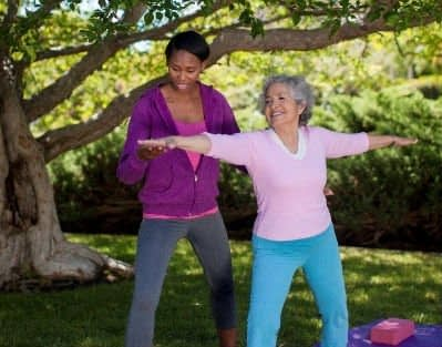 Older woman in pink sweater doing yoga outside in Dayton, OH