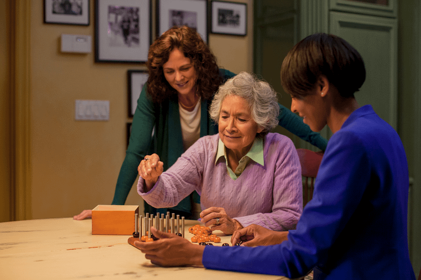 Older woman playing a board game with her daughter and a home care assistant in Burlington, VT