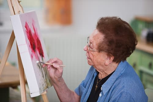 A senior woman enjoying painting in her home