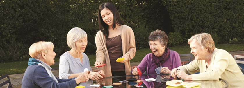 Group of senior women playing cards with a home care assistant in Burlington, VT