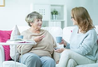 A senior woman having an engaging conversation in her home with a caregiver