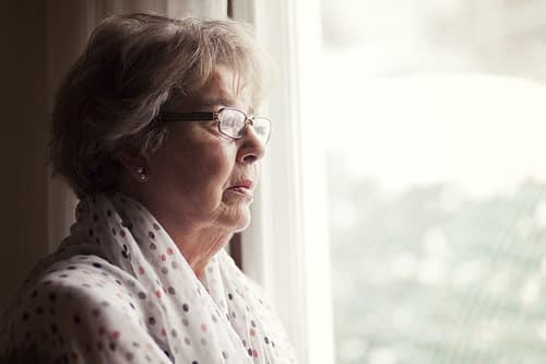 Senior woman waiting by the window for home care provider