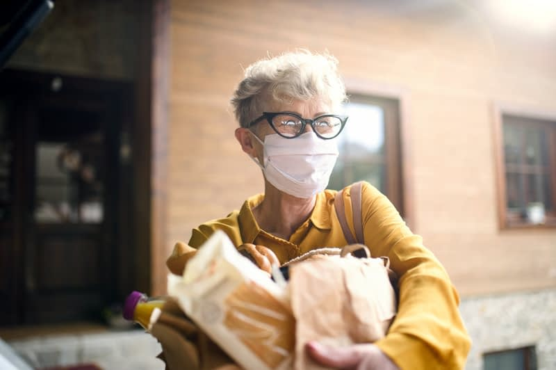 elderly woman in mask holding groceries